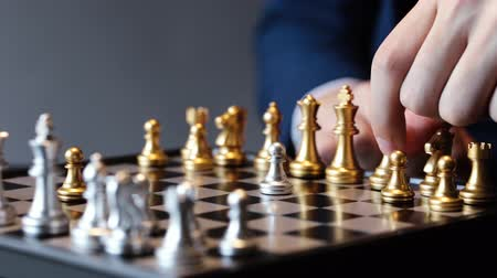 rycerze : Unrecognizable male in suit making a move in chess play against gray background Wideo
