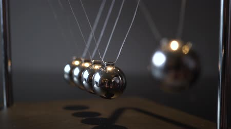 oneindig : Close-up video of metal Newton cradle swining on gray background as representation of momentum concept