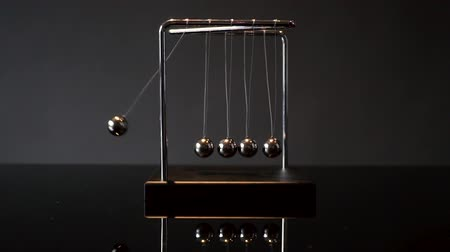 lendület : hands pulling ball of metal Newton cradle and observing momentum Stock mozgókép