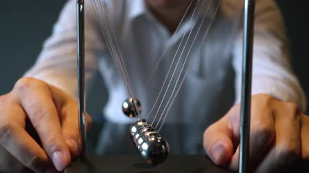 lendület : Unrecognizable blurred male pulling ball of metal Newton cradle and observing momentum