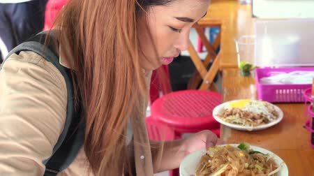 krewetki : Young Asian tourist woman eating pad thai noodle, traditional street food in Thailand and looking at camera