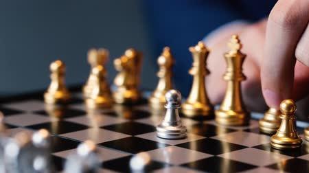 estratégico : Unrecognizable male in suit making a move in chess play against gray background Stock Footage