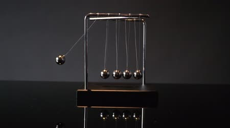 lendület : Closeup video of metal Newton cradle swining on gray background as representation of momentum concept