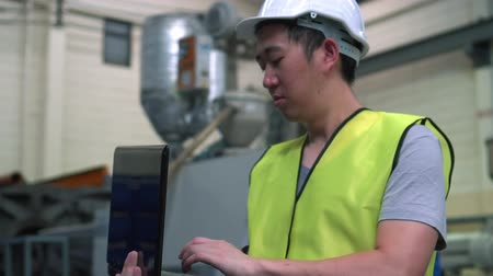 tesisler : Asian male Industrial engineer in hard hat working with laptop in safety jacket at heavy industry manufacturing factory. Processing plastic injection molding industry