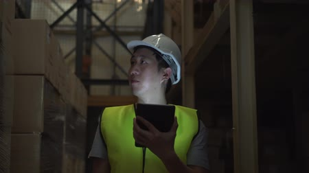 hard hat : Asian young warehouse worker man with safety hard hat is walking through inventory room, checking order details with a digital tablet Stock Footage