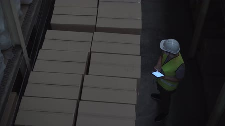 осмотр : Top view of young warehouse worker man with safety hard hat is checking order details with a digital tablet at inventory room
