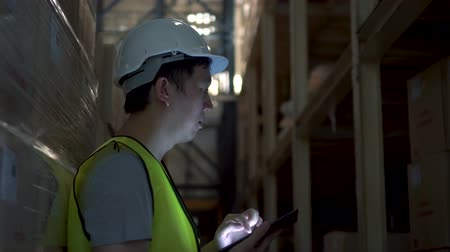 jelölőnégyzetet : Side view of Asian young warehouse worker man with safety hard hat is checking order details with a digital tablet at inventory room