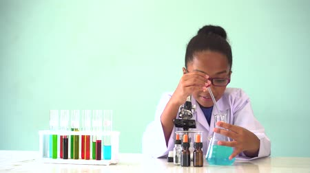 laboratorní plášť : Young African American mixed kid testing chemistry lab experiment and shaking glass tube flask along with microscope and smile - science and learning education concept