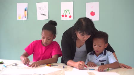 etnia africano : Young teacher giving African American kids an art lesson and teaching how to draw inside indoors room in natural ambient light
