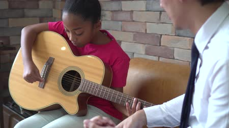 strum : Young Asian male teacher giving a guitar lesson and teaching how to play guitar to African American girl in indoors room