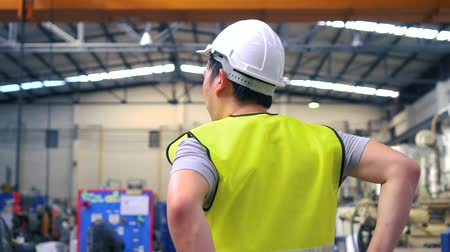 навес : Back view of Asian industrial engineer in helmet and waistcoat doing stretching exercises while relaxing during break on factory Стоковые видеозаписи
