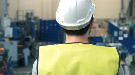 инспектор : Close up rear view of factory worker with safety hard hat is walking through industrial facilities at heavy industry manufacturing factory