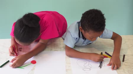biblioteca : African American kids learning how to draw with crayon on table inside indoors room in natural ambient light Stock Footage