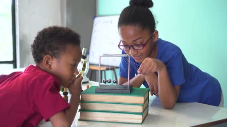 lendület : Two African American mixed kids using a magnifying glass and pulling a newtons cradles ball swing in science classroom - fun learning education concept