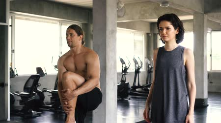 coxa : Young woman and man stretching their legs on the gym floor. Two people couple working out indoors Stock Footage