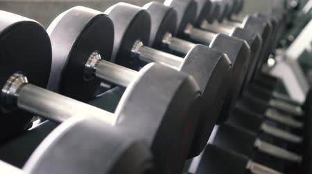 libras : Dolly shot of dumbbells and barbells row in modern sport club gym