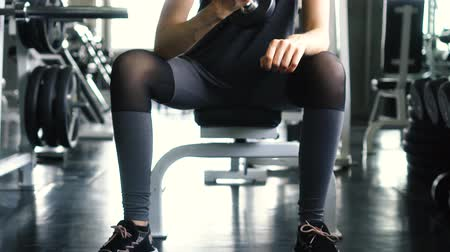 biceps curls : Young woman in sportswear doing seated dumbbell concentration curl bicep exercise at the gym Stock Footage