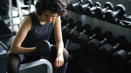 férfiasság : Young Caucasian woman in sportswear doing seated dumbbell concentration curl bicep exercise at the gym