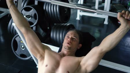 břišní : Shirtless muscular young man doing barbell bench press exercise at the gym