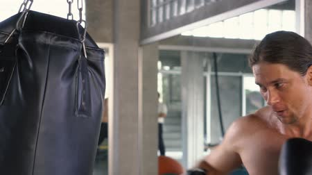 feroz : Powerful shirtless male punching bag fiercely while boxing on blurred background of modern gym Vídeos