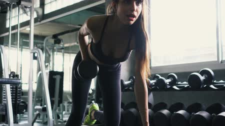 ohnutý : Young Caucasian fitness woman doing bent over dumbbell row exercise at the gym