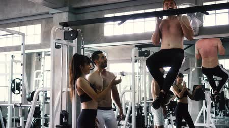 pulling up : Male and female friends cheering man practicing chin ups exercise on bars at the gym Stock Footage