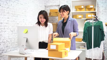 sme : Two young Asian adult fashion business female merchant sellers in the office working at online business company with parcels of clothing to be delivered