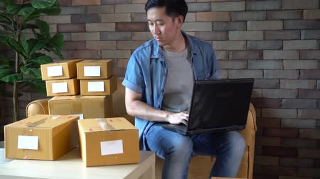 sme : Young Asian male business entrepreneur using computer laptop while packing products into boxes to deliver customers from online orders ready to ship