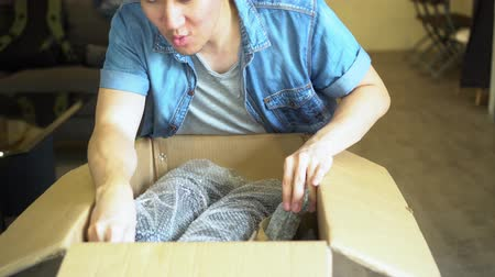 удивительный : Young excited Asian man open box with product wrapped in plastic in living room