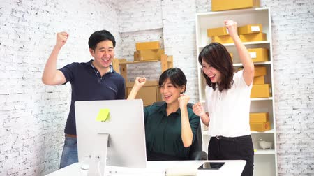 emelt : Asian businessman and businesswoman celebrating success and victory in small office