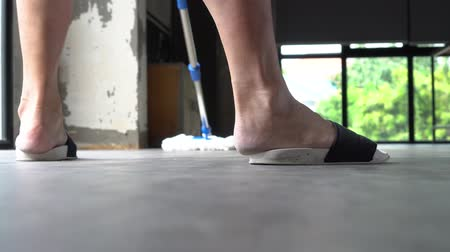 szandál : Low section of human legs and feet wearing slippers using mopping tool to clean up inside the living room at home - cleanliness and housekeeping concept