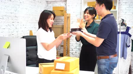 each other : Asian male co-worker walking and giving a surprise birthday to female colleagues and blowing candles on cake while celebrating birthday in office Stock Footage