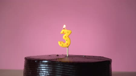 três : Chocolate birthday cake on pink background with yellow number three candle in middle electric lighter lighting candle making wish trying to blow out candle Stock Footage