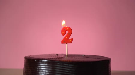 повод : Chocolate birthday cake on pink background with red number two candle in middle electric lighter lighting candle making wish trying to blow out candle