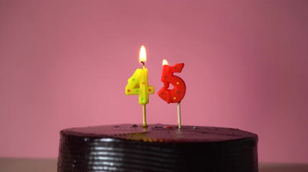 čtyřicet : Chocolate birthday cake on pink background with yellow and red number forty five candle in middle electric lighter lighting candle