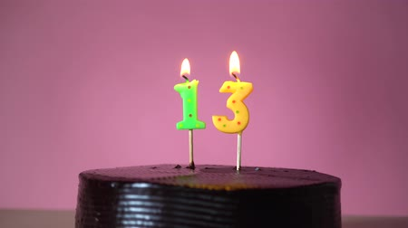 中世の : Chocolate birthday cake on pink background with green and yellow number thirteen candle in middle electric lighter lighting candle making wish trying to blow out candle