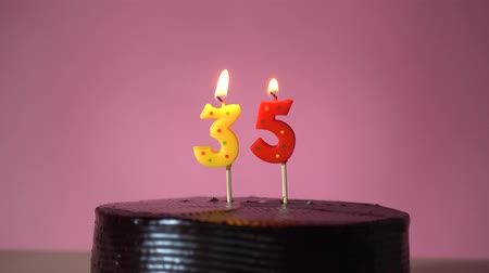 otuzlu yıllar : Chocolate birthday cake on pink background with yellow and red number thirty five candle in middle electric lighter lighting candle Stok Video