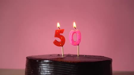 中世の : Chocolate birthday cake on pink background with red and yellow number fifty candle in middle electric lighter lighting candle