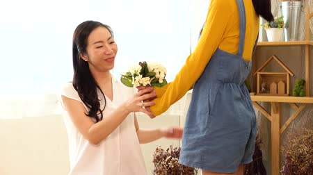 hidden face : Face of Asian teenage daughter hugging and kissing happy smiling middle-aged mother with tenderness in indoor living room at home. Mother is holding a bouquet received from child. Mothers day concept