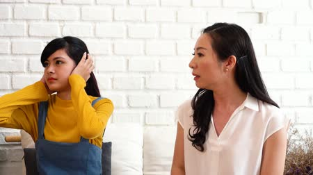 resentment : Argument between annoyed Asian teenage daughter and upset middle aged mother. The child covering ears while mum arguing. Bad, unhealthy, toxic family relationship concept