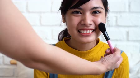 corar : Makeup artist applying make-up for young Asian teenage girl. Female teenager smiling with makeup brush on her face cheek on white brick wall background