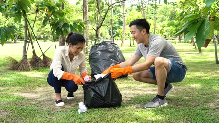 wolontariat : Young Asian man and woman wearing orange gloves and collecting trash in garbage bag in the park. Save the earth and environmental concern concept Wideo