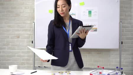 naam : Young smiling business woman holding a tablet checking financial and account documents at office