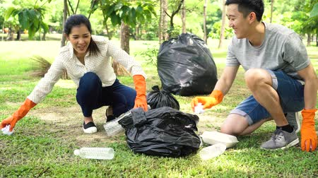 preoccupazione : Young Asian man and woman wearing orange gloves and collecting trash in garbage bag in the park. Save the earth and environmental concern concept Filmati Stock
