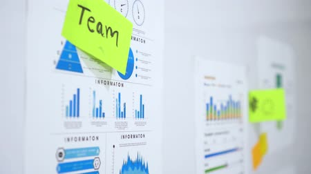 task : Person sticking note with sign of team work on colourful graph on office whiteboard Stock Footage