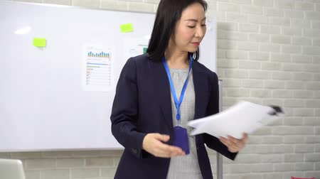 femminismo : Satisfied Asian woman in formal outfit with badge smiling and reading paper while standing by table with marketing plan and laptop in office
