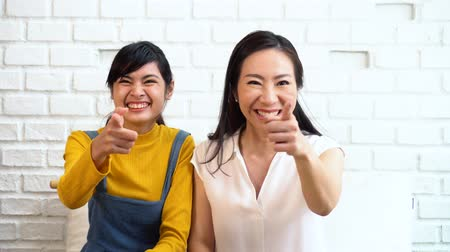 aanmoedigen : Asian family of mother and daughter smiling while cheering at home and watching TV on white brick wall background