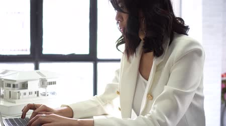 miniatűr : Young Asian female architect using a laptop with house model behind in the background. Beautiful woman focused and determined with creativity at studio office