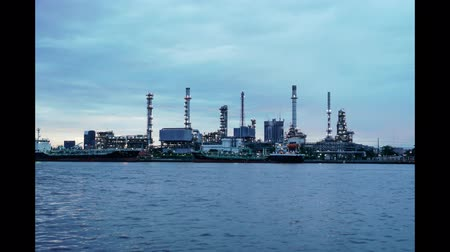 refining : Day to night timelapse video of petroleum oil refinery plant beside river in twilight time. Crude Oil Process machinery Stock Footage