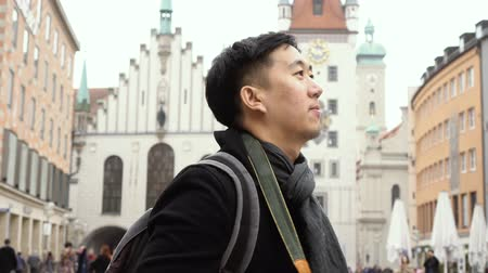 münchen : Young Asian traveling backpacker in city centre in Europe. Man taking photos in Marienplatz square, Munich, Germany. Traveling to Europe